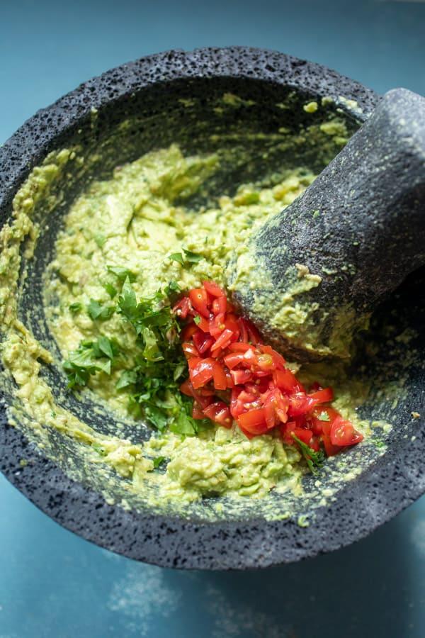 Adding tomatoes to guacamole