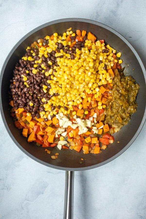 Corn and black beans added to enchilada vegetables.