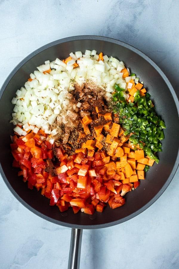 Vegetables for enchilada casserole in a skillet.