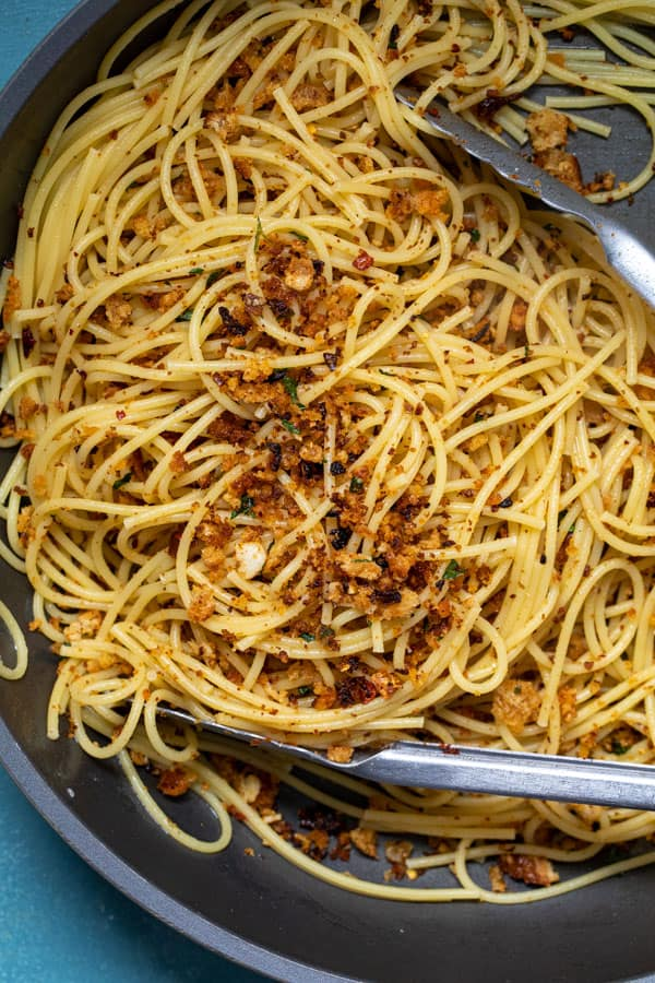 Mixing in breadcrumbs into cooked spaghetti.