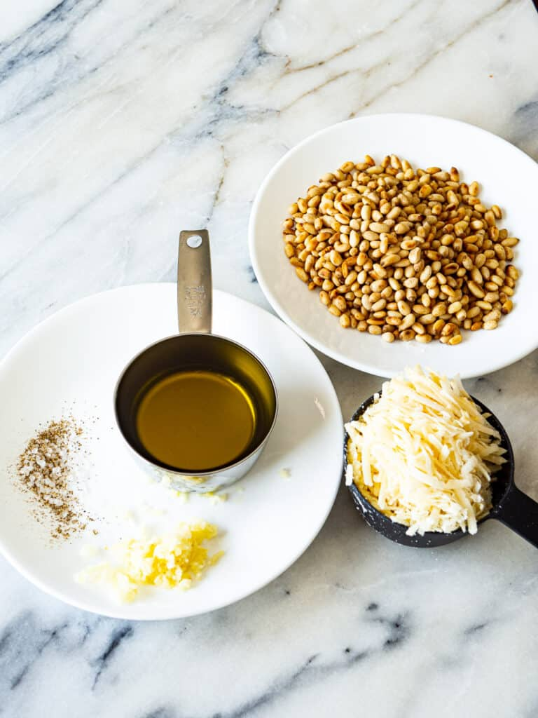 Toasted pine nuts, olive oil, and garlic next to a cup of grated cheese
