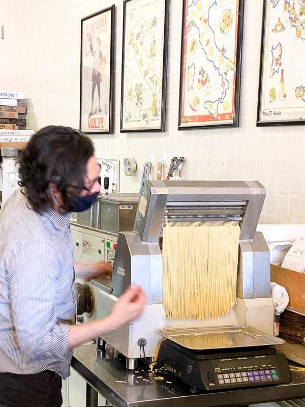A man feeding pasta through a pasta-cutting machine