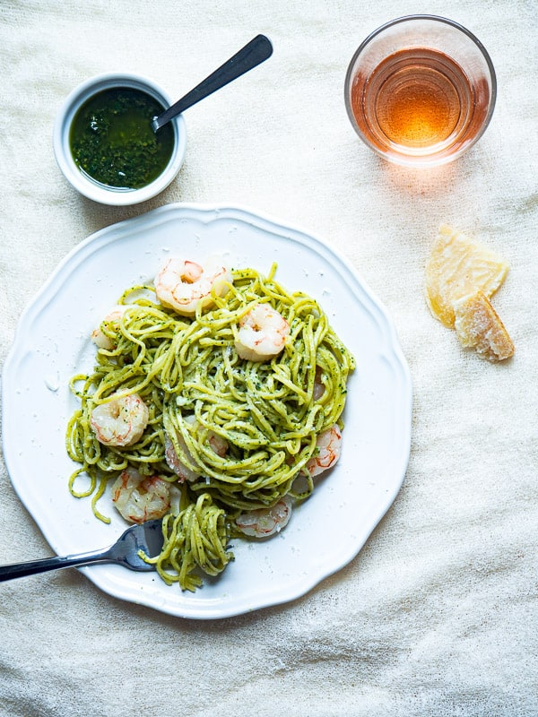 A plate of pasta and shrimp tossed in pesto next to more pesto and cheese.