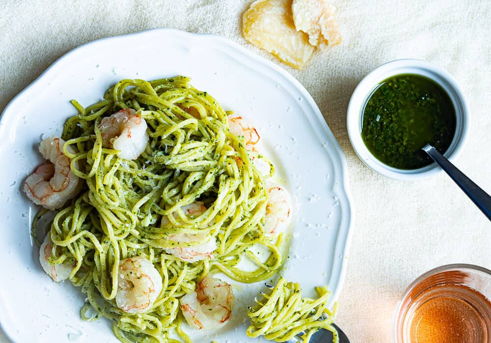 A plate of pasta and shrimp with pesto next to a container of pesto